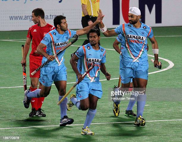 Indian hockey player Sandeep Singh celebrates with team members after scoring a goal during the FIH London Olympics men's hockey qualifying match...