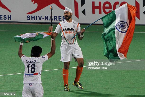 Indian hockey player Sandeep Singh celebrates with the Indian national flag after beating France 81 during the final of the FIH London Olympics Men's...