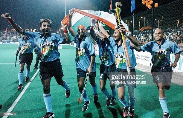 Indian hockey players Gagan Ajit Singh Prabhjot Singh Sandeep Michael Dileep Tirkey and Len Ayiappa carry a national flag as they do a victory lap of...