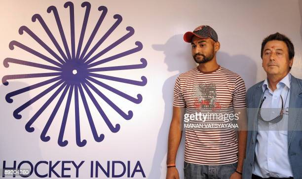 Indian hockey team captain Sandeep Singh and coach Jose Brasa pose with the newly unveiled team logo in New Delhi on July 23 2009 A 23member Indian...