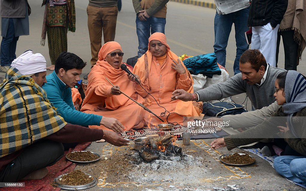 Indian holy women (C) and demonstrators perform a prayer ritual in memory of a gangrape victim in New Delhi on January 2, 2013. The family of an Indian gang-rape victim said that they would not rest until her killers are hanged as police finalised their investigation before charges are laid against suspects this week. As the ruling Congress party reportedly pushed for tougher punishments for sex crimes, including chemical castration, authorities in New Delhi launched a hotline to improve safety for women in a city dubbed 'India's rape capital'. AFP PHOTO/RAVEENDRAN