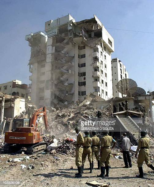 Indian Home Guards watch an excavator dig into the rubble of a tenstorey apartment as they search for survivors 29 January 2001 in Ahmedabad...