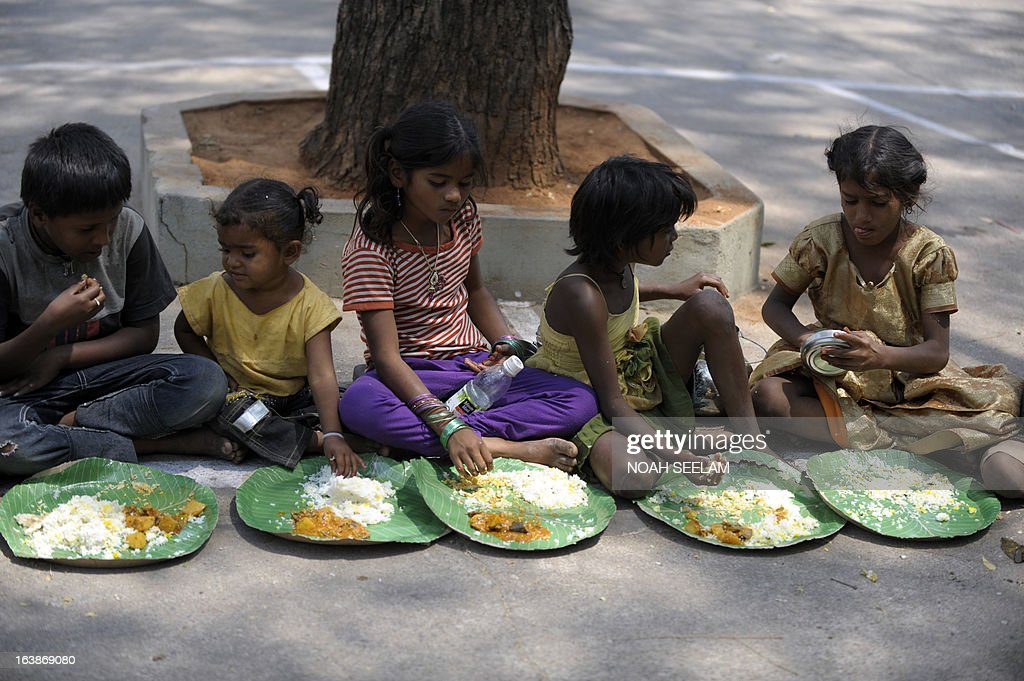 Indian homeless eat food at a feeding programme for the poor in Hyderabad on March 17, 2013. India still has the worlds largest number of impoverished in a single country, of its nearly one billion inhabitants, an estimated 350-400 million live below the poverty line with 75 percent of them in the rural areas. AFP PHOTO / Noah SEELAM