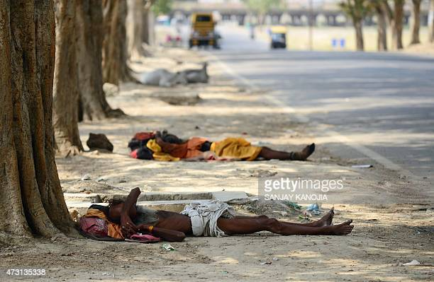 Indian homeless men rest under trees on a hot summer day in Allahabad on May 13 2015 AFP PHOTO/ SANJAY KANOJIA