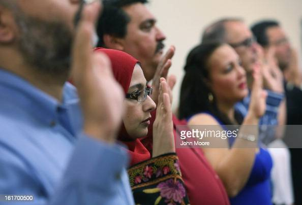 Indian immigrant Arshi Khan takes the oath of citizenship while becoming American citizens at a special Valentines Day naturalization ceremony for...