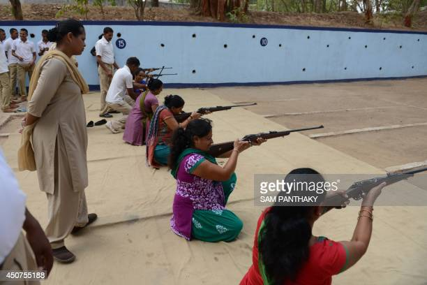 Indian instructors keep watch as participants fire 22 bore rifles during a fiveday firearms training programme for women aged 15 and above at the...