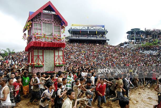 Indian Jaintia tribesmen transport a 'Rath' or chariot and dance in muddy waters during the celebration of the Behdienkhlam festival in Jowai some 64...