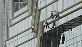 Indian janitors clean the facade of a highrise building in Mumbai on April 27 2015 India's economy will grow much faster than forecast this year and...