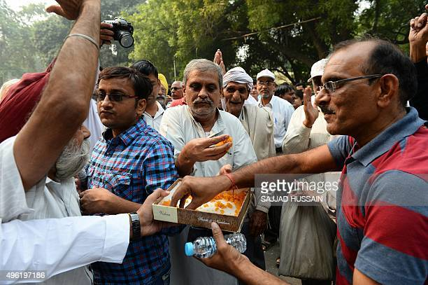 Indian Janta Dal United activists and supporters distribute sweets as they celebrate after a victory by an alliance led by their party in New Delhi...