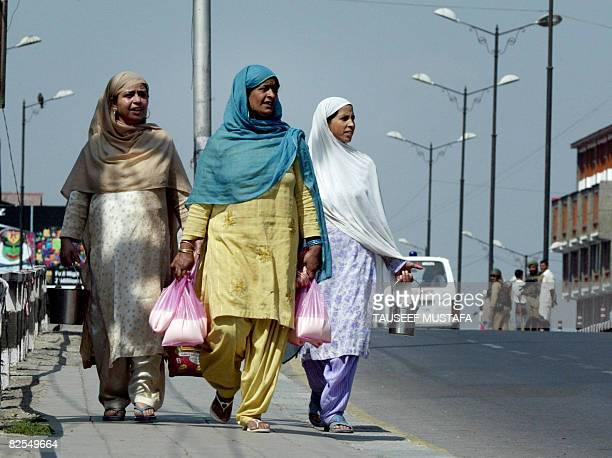 Indian Kashmir women walk with groceries in Srinagar on August 26 as Indian security personnel enforce a curfew Indian security forces opened fire on...