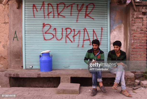 Indian Kashmiri men sit next to graffiti that reads 'Martyr Burhan' in reference to the slain rebel leader during a curfew in Srinagar on July 8 2017...