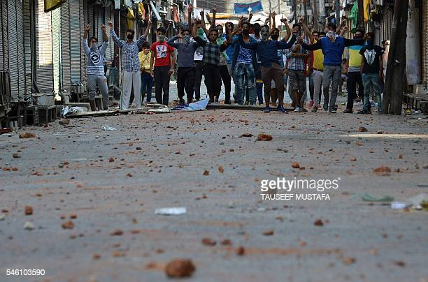 Indian Kashmiri protestors cheer in front of rocks on the ground thrown during clashes with police in Srinagar on July 11 2016 Police said 30 people...