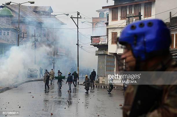 TOPSHOT Indian Kashmiri protestors throw stones at police who fired tear smoke shells during clashes in downtown Srinagar on January 29 2016 Police...