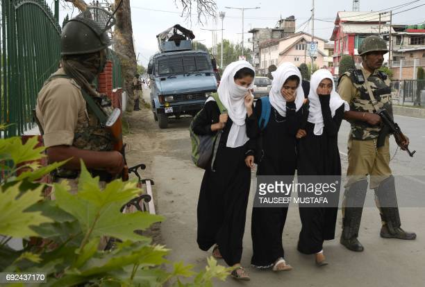 Indian Kashmiri students walk past Indian government forces standing guard in central Srinagar on June 5 2017 Indian paramilitary forces killed four...