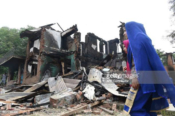 TOPSHOT Indian Kashmiri villagers walks near the debris of houses destroyed during a gunfight between rebels and Indian government forces at Bahmnoo...