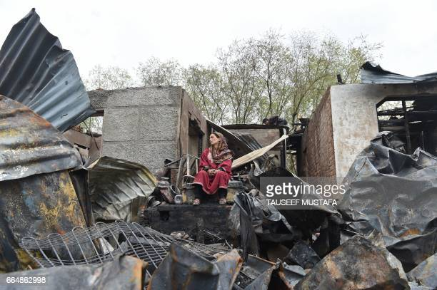 TOPSHOT Indian Kashmiri woman sits near her gutted residential houses in the interiors of dal lake in Srinagar on April 5 2017 About 30 residential...