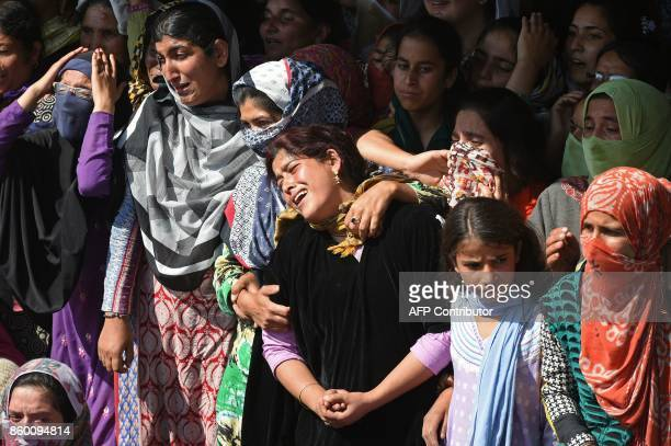 Indian Kashmiri women and girls watch the funeral procession of slain militant Nasarullah Mir at Hajin village in Bandipora district north of...