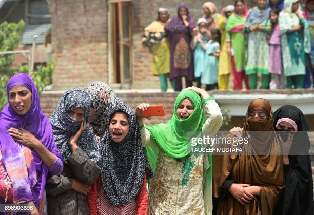 Indian Kashmiri women watch the funeral procession for LashkarEToiba district rebel commander Junaid Matoo in the village of Khudwani south of...