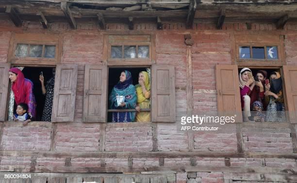 Indian Kashmiri women watch the funeral procession of slain militant Nasarullah Mir at Hajin village in Bandipora district north of Srinagar on...
