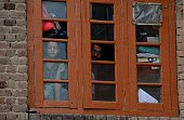 Indian Kashmiris look through a window inside a house as Indian paramilitary troopers patrols outside on the 14th day of a curfew in downtown...