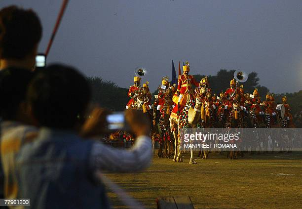 Indian kids click pictures of The Indian Border Security Force band riding on camels during the BSF Tattoo in New Delhi 17 November 2007 The word...