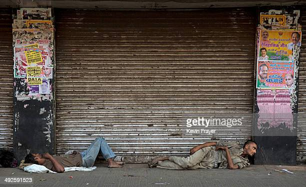 Indian laborers lay on the pavement under posters celebrating BJP leader Narendra Modi's election victory on May 21 2014 in Delhi India India elected...