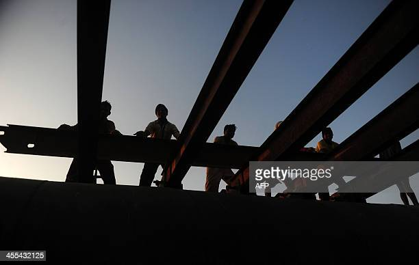 Indian laborers push a girder to construct a temporary pontoon bridge over the River Ganges for the upcoming Magh Mela festival in Allahabad on...