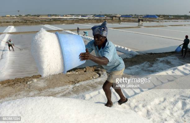 Indian labourer Karupasamy empties a basket of salt as he works on a salt pan at Thoothukudi some 160kms south of Madurai on May 14 where labourers...