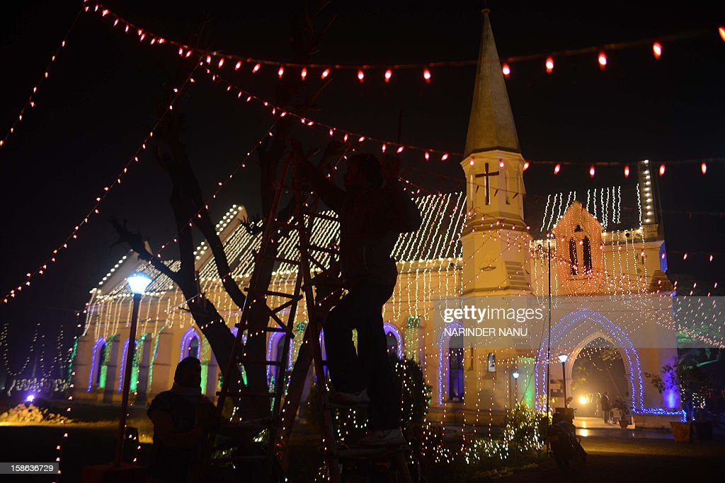 Indian labourers adjust lights at the illuminated St Paul's church in Amritsar on December 22, 2012. Despite Christians forming a little over two percent of the billion plus population in India, with Hindus comprising the majority, Christmas is celebrated with fanfare and zeal throughout the country.