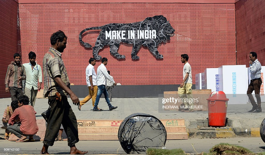 Indian labourers and pedestrians walk past a wall bearing the image of the mascot at the venue for the 'Make in India Week' in Mumbai on February 12, 2016. Over 190 companies, and 5,000 delegates from 60 countries, are due to take part in the first 'Make in India' week to be held in Mumbai from February 13-18. AFP PHOTO / INDRANIL MUKHERJEE / AFP / INDRANIL MUKHERJEE
