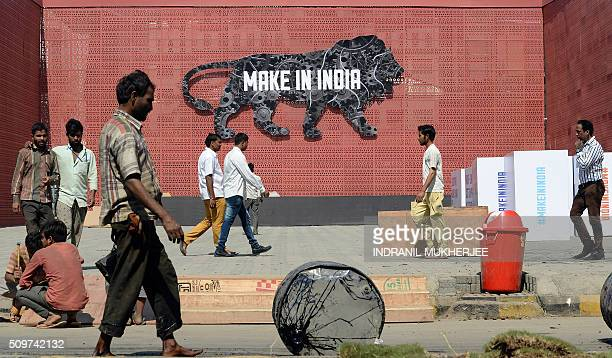 Indian labourers and pedestrians walk past a wall bearing the image of the mascot at the venue for the 'Make in India Week' in Mumbai on February 12...