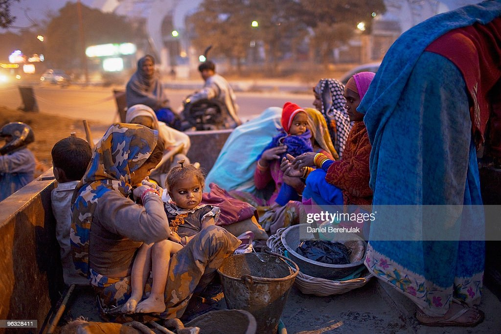 Indian labourers and their children sit in the back of a tractor before being transported to their temporary tent dwellings after working at a construction project in front of the Jawaharlal Nehru Stadium on February 01, 2010 in New Delhi, India. The children accompany their parents to the work site, where if they are prepared to work, they will receive money for bread and milk and be provided with dinner by the contractor. The Commonwealth Games are due to be held in the Indian capital from October 3-14, 2010, but concerns remain over construction of its sporting and transport infrastructure. The sheer scale of the project has drawn an enormous population of migrant workers from all over India. This week the High Court of Delhi has sought a response from the Government over the alleged failure to provide all the benefits of labour laws to workers involved in construction work for the coming Commonwealth Games. Workers are being paid below the minimum wage in order to complete these projects whilst also being forced to live and work under sub standard conditions.
