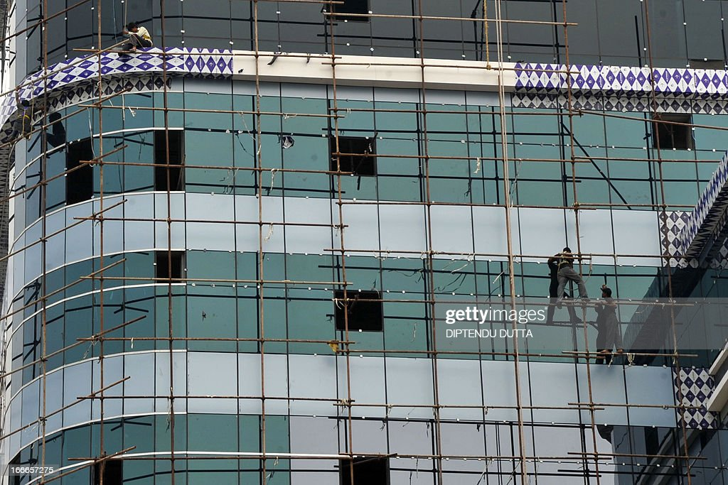 Indian labourers are seen at work on a high-rise building in Siliguri on April 15, 2013. India's inflation unexpectedly slipped to below six percent for the first time in nearly three and half years, official data showed on Monday, fanning hopes of fresh interest rate cuts. AFP PHOTO/Diptendu DUTTA