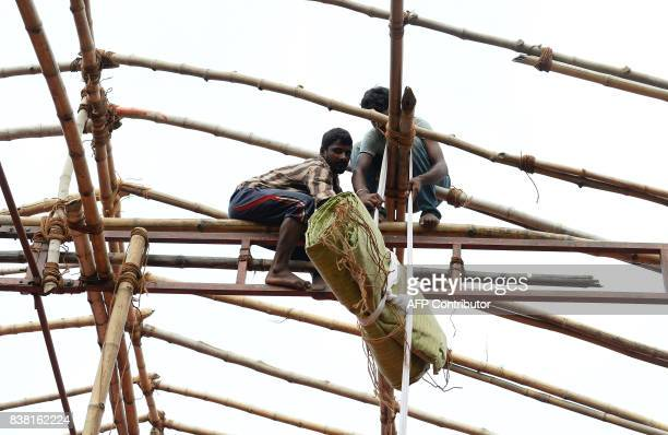 Indian labourers balance on bamboo poles as they erect a temporary shelter for an event in New Delhi on August 24 2017 / AFP PHOTO / SAJJAD HUSSAIN