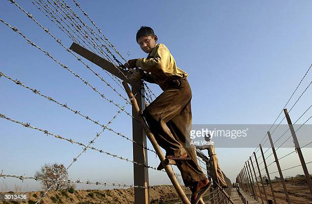 Indian labourers build a fence separating India and Pakistan along the International Border on February 25 2004 near Ahknoor India With the recent...