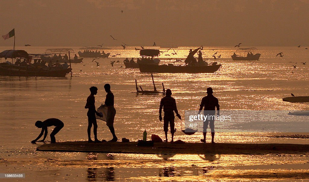 "Indian labourers carry a basket to clean the banks of the Ganga River as devotees take a holy dip in the 'Sangam,"" the confluence of the three rivers Ganges, Yamuna and mythical Saraswati in Allahabad on December 22, 2012, ahead of the Mahakumbh Mela. The Kumbh Mela, which is scheduled to take place in the northern Indian city in January and February 2013, is the world's largest gathering of people for a religious purpose and millions of people gather for this auspicious occasion. AFP PHOTO/ Sanjay KANOJIA"