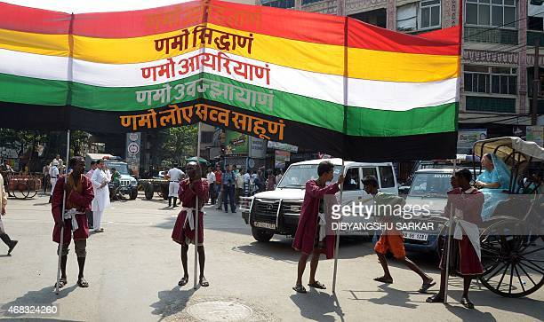 Indian labourers carry a Jain inspired banner as a hand pulled rickshaw passes during a religious rally organised on the occasion of Mahavir Jayanti...