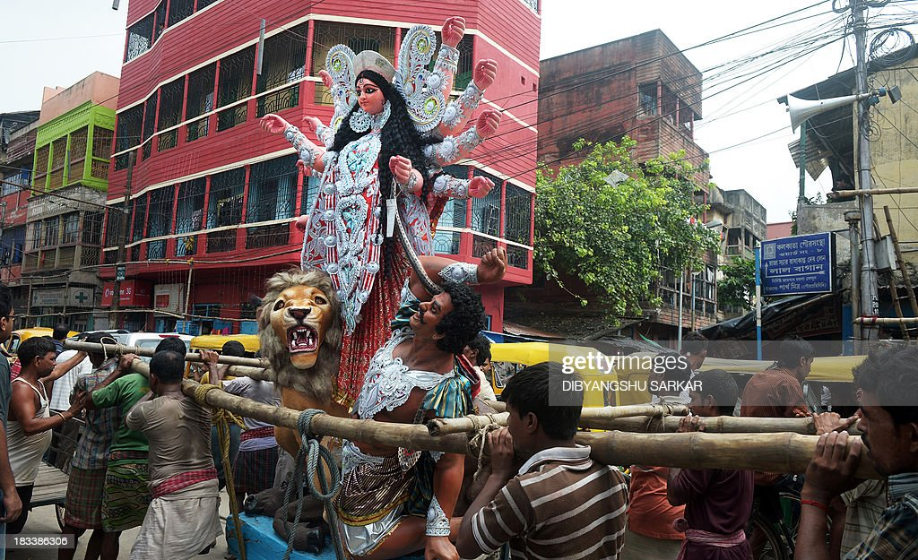 Indian labourers carry a statue of the Hindu goddess Durga from a workshop in Kumartoli, the idol makers' village, to a truck to be sent to a place of worship in Kolkata on October 6, 2013. Late monsoon rain and rising inflation add to the difficulties of the artisans in their business ahead of the five-day Durga Puja festival celebrated in October. AFP PHOTO/ Dibyangshu SARKAR