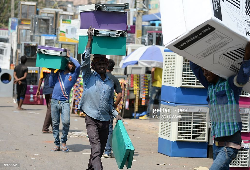 Indian labourers carry parts of a water cooler at a market in the old quarters of New Delhi on May 1, 2016. / AFP / SAJJAD