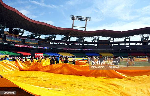 Indian labourers clear water off the plastic covers from the grounds ahead of the first One Day International cricket match between India and...
