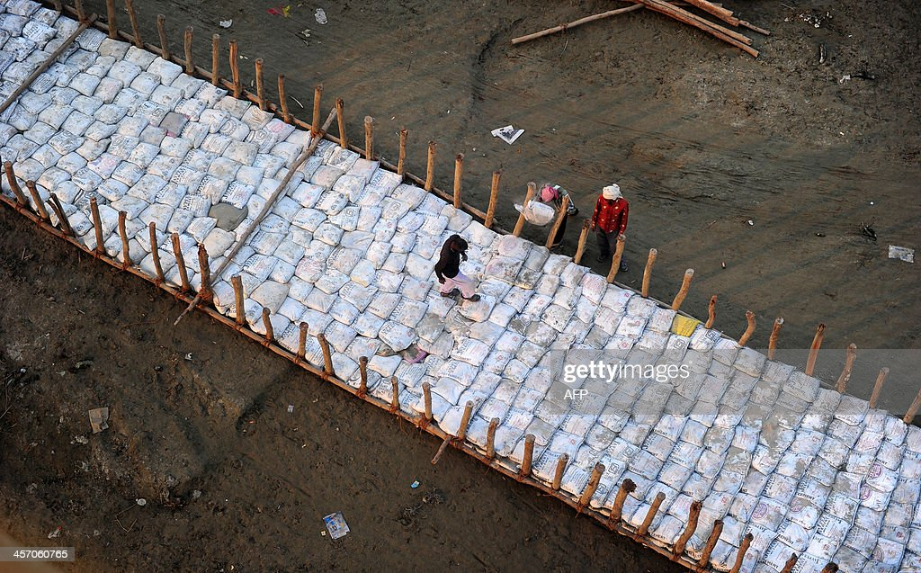 Indian labourers construct a temporary road with sand bags on the dry river bed area in preparation for the annual Hindu religious fair of Magh Mela...