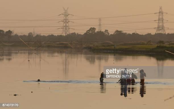 Indian labourers cross the Mahananda river after work on the outskirts of Siliguri on November 14 2017 / AFP PHOTO / DIPTENDU DUTTA