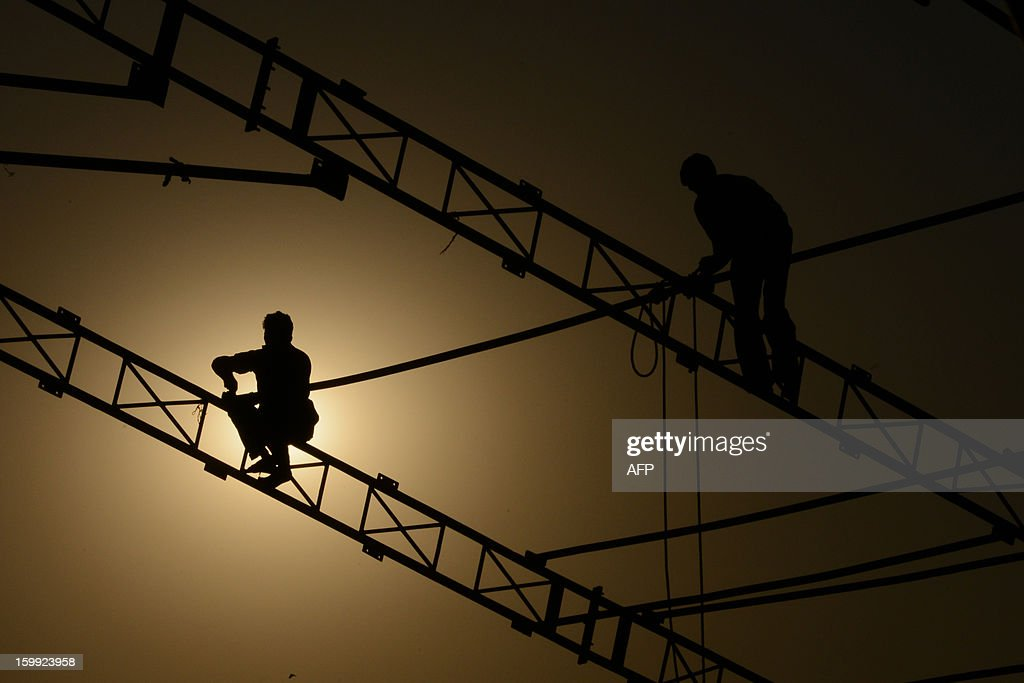 Indian labourers erect a temporary exhibition dome in Ahmedabad on January 23, 2013. In India the labourers do risky jobs and earn very little with the Indian economy gradually growing owing to a skilled labour force. AFP PHOTO / Sam PANTHAKY
