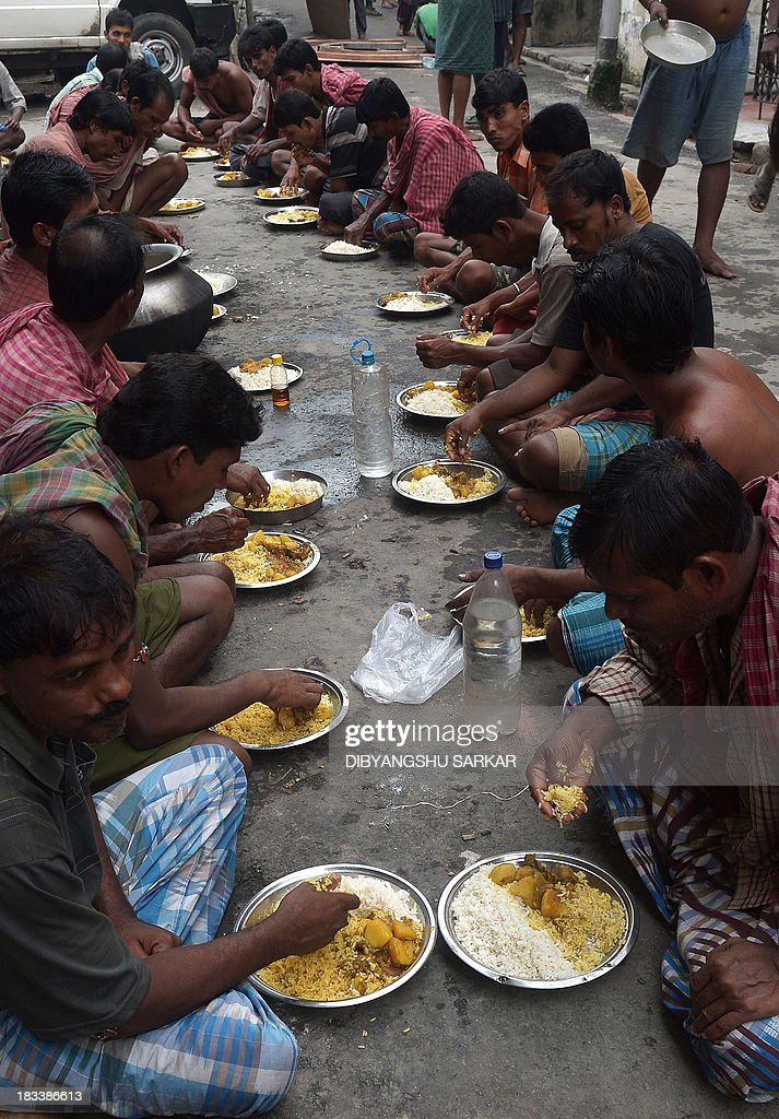 Indian labourers have their lunch prior to carrying a finished clay statue of the Hindu goddess Durga from a workshop in Kumartoli, the idol makers' village to a place of worship in Kolkata on October 6, 2013. Late monsoon rain and rising inflation add to the difficulties of the artisans in their business ahead of the five-day Durga Puja festival celebrated in October. AFP PHOTO/ Dibyangshu SARKAR