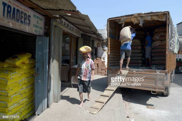 Indian labourers load a truck with sacks of food grain at the APMC wholesale trading market in Bangalore on February 28 2017 India's economic growth...