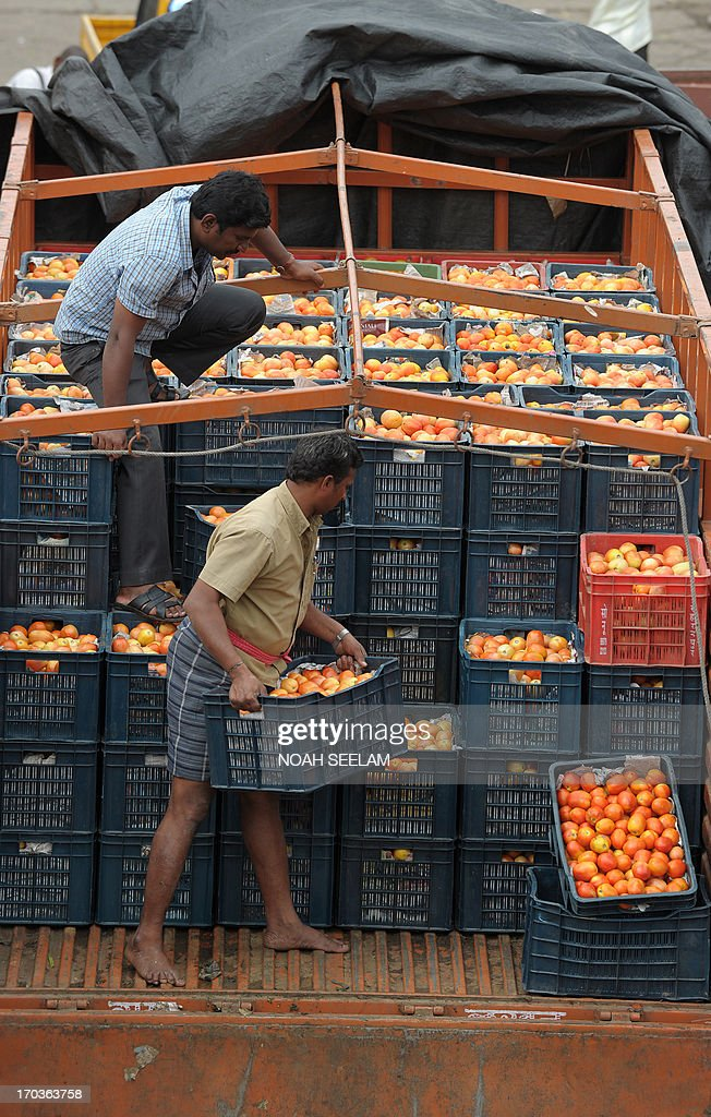Indian labourers load containers of tomatoes onto a truck at a vegetable wholesale market in Hyderabad on June 12, 2013. The National Food Security Bill - 2011, considered to be the world's largest experiment in ensuring food security to the poor, has been a key project of Congress president Sonia Gandhi and finally seems to be getting off the ground at a whopping cost of 1.25 lakh crore Indian rupees. The Bill aims at meeting the food needs of 75% of rural households and 50% of urban households. AFP PHOTO / Noah SEELAM