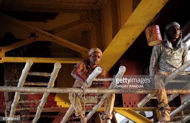 Indian labourers paint the Naini railway bridge in Allahabad April 27 2017 / AFP PHOTO / Sanjay KANOJIA