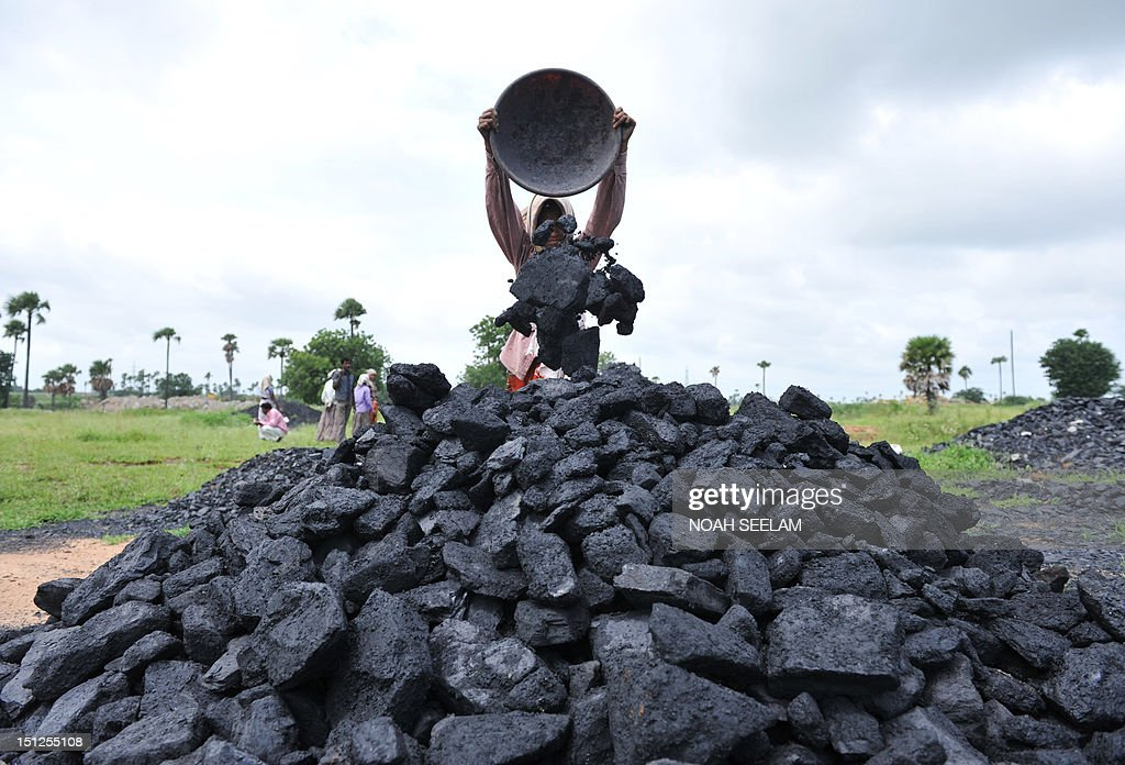 Indian labourers pile coal at a coal field on the outskirts of Hyderabad on September 5 2012 Indian police on September 4 opened a probe into five...