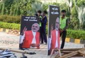 Indian labourers prepare a poster of Bharatiya Janata Party party Prime Ministerial candidate Narendra Modi at a function to kick off the BJP...