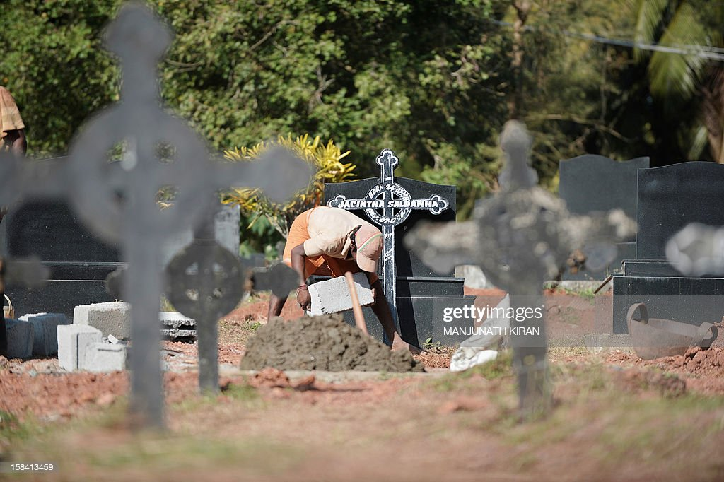 Indian labourers prepare the grave of Jacintha Saldanha, 46, at the Shirva Church Cemetery at her in laws village, north of Mangalore on December 16, 2012. The body of an Indian-born nurse, Saldanha, found dead after taking a hoax call to the hospital treating Prince William's wife was due to arrive in Mangalore following a mass in her memory held in London. Saldanha was found hanged days after answering the prank telephone call from two Australian radio DJs posing as British royals to the hospital where Catherine was admitted during the early stages of her pregnancy. AFP PHOTO/ Manjunath Kiran